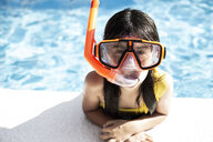 Portrait of little girl wearing snorkel and oversized diving goggles leaning on poolside - ERRF00162