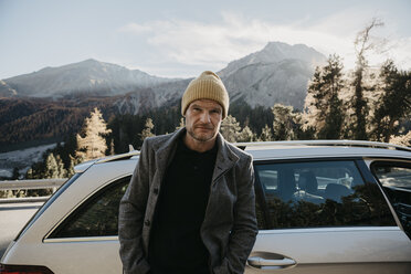 Man travelling through Switzerland, standing by his car - LHPF00179