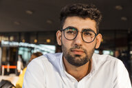 Portrait of pensive young businessman with beard and glasses at sidewalk cafe - TCF05973