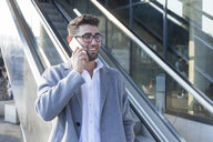 Portrait of smiling young businessman on the phone - TCF05982