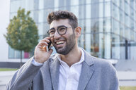 Portrait of laughing young businessman on the phone - TCF05985