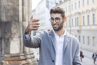 Germany, Munich, portrait of young businessman taking selfie with cell phone in the city - TCF05988