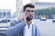 Germany, Munich, portrait of young businessman on the phone - TCF05991