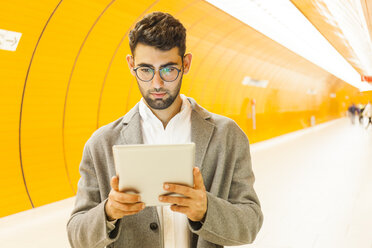 Germany, Munich, portrait of young businessman using digital tablet at underground station - TCF05997