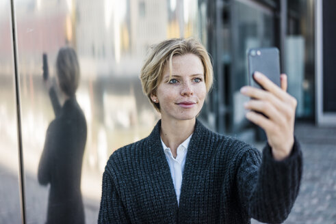 Young businesswoman taking selfie with her smartphone - MOEF01695