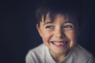 Cheerful boy with gap toothed looking away in darkroom - CAVF56463