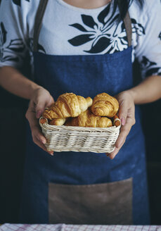 Midsection of woman holding croissants in basket at kitchen - CAVF56523