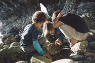 Friends playing with rocks while crouching at beach - CAVF56526
