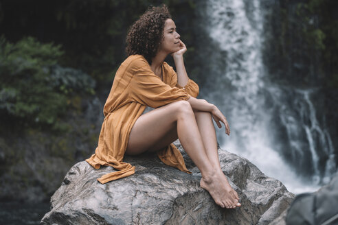 Thoughtful woman looking away while sitting on rock against waterfall in forest - CAVF56532