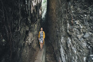 Woman walking amidst rock formations in forest - CAVF56535