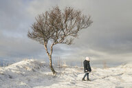 Full length of girl standing by bare tree on snowy field - CAVF56541