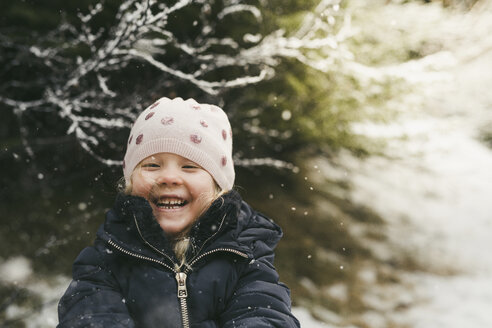 Cheerful girl playing outdoors during winter - CAVF56544