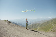 Hiker flying kite against mountains and sky during sunny day - CAVF56595