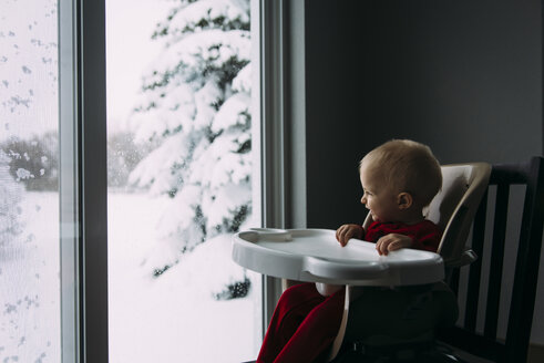 Happy baby boy looking through window while sitting on high chair at home during winter - CAVF56613