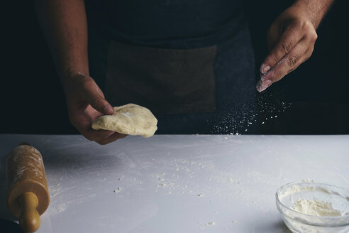 Midsection of baker sprinkling flour on table while holding dough - CAVF56625