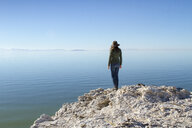Rear view of woman standing on rock at Antelope Island against clear blue sky - CAVF56640