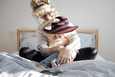 Happy mother with shirtless daughter wearing hat while sitting on bed at home - CAVF56649