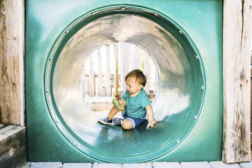 Full length of baby boy sitting in tube at playground - CAVF56658