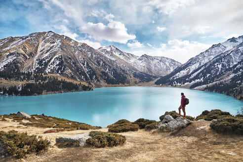 Full length of backpacker looking at view while standing by lake against mountains and cloudy sky during winter - CAVF56664