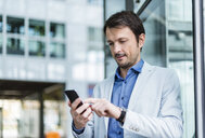 Portrait of a businessman using smartphone in the city - DIGF05496