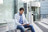 Businessman sitting on a bench, using digital tablet - DIGF05505