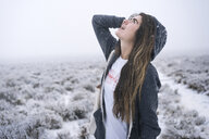 Woman with long hair looking up while standing on snow covered field - CAVF56669