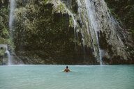 Rear view of shirtless man swimming in river by waterfall at forest - CAVF56687