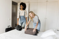 Two smiling women with baggage arriving in accomodation - VABF01842