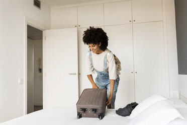 Smiling woman placing suitcase on bed - VABF01845
