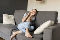 Smiling young woman with closed eyes sitting on couch talking on cell phone - VABF01851