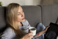 Young woman sitting on couch holding coffee cup and tablet - VABF01854