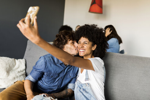 Happy couple sitting on couch taking a selfie - VABF01863