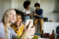 Happy girlfriends sitting at dining table taking a selfie - VABF01875