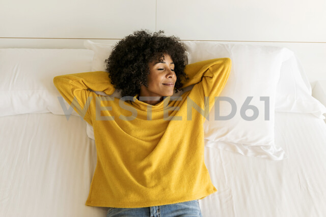Smiling woman with closed eyes lying on bed - VABF01932