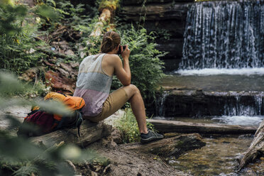 Back view of hiker in a forest taking photo of waterfall - VPIF01169