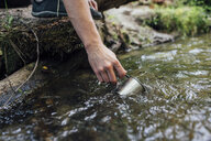 Young man's hand scooping fresh water from a brook, close-up - VPIF01172