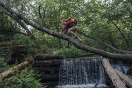 Young hiker with backpack crossing water on tree trunk in the forest - VPIF01178