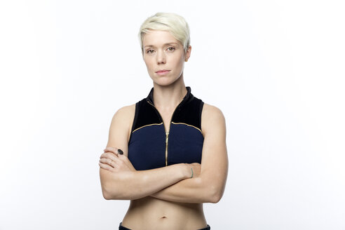 Portrait of serious looking woman with short blond dyed hair in front of white background - FLLF00049