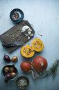 Sliced and whole Hokkaido pumpkin, onions, garlic and herbs on wood - ASF06260