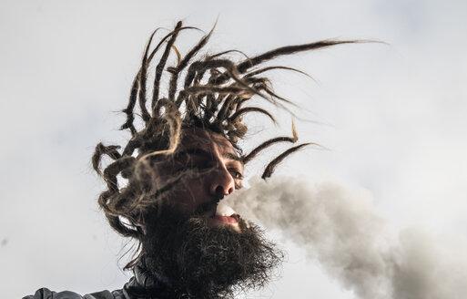 Bearded man with dreadlocks smoking and moving - OCMF00116
