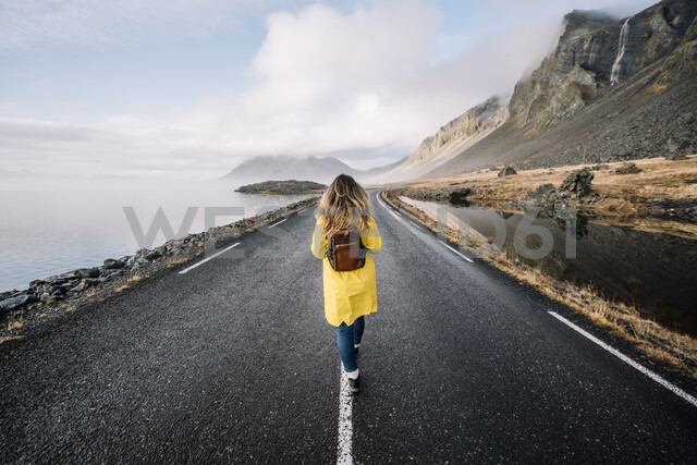 Iceland, back view of woman with backpack walking on median strip of country road - OCMF00120 - Oscar Carrascosa Martinez/Westend61