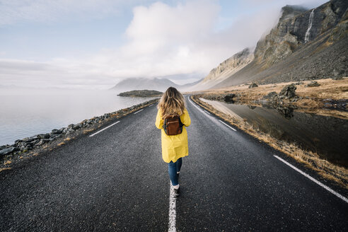 Iceland, back view of woman with backpack walking on median strip of country road - OCMF00120