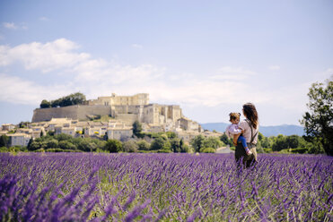 France, Grignan, mother standing in lavender field with little daughter on her arms looking at village - GEMF02586