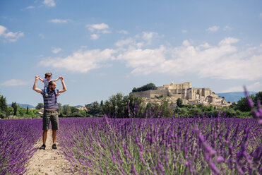 France, Grignan, father standing on foot path between lavender fields with little daughter on his shoulders - GEMF02601