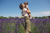 France, Grignan, mother kissing little daughter in lavender field - GEMF02619