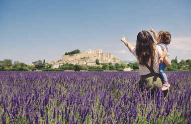 France, Grignan, back view of mother and little daughter standing together in lavender field looking up - GEMF02622