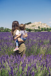 France, Grignan, back view of mother and little daughter standing together in lavender field looking at village - GEMF02625