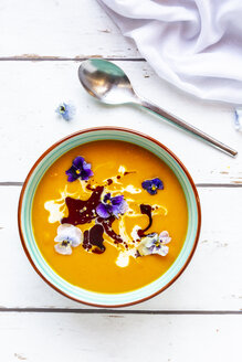 Bowl of creamed pumpkin soup garnished with edible flowers - SARF03986