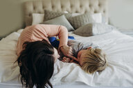 Happy mother playing with son while lying on bed at home - CAVF56779