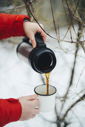 Cropped hands of woman pouring black coffee from insulated drink container into mug during winter - CAVF56791